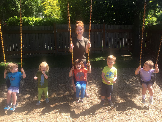 teacher with children on swings